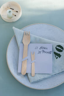 Germany, Plate, cloth napkin and DIY menu with wooden forks - GISF00571