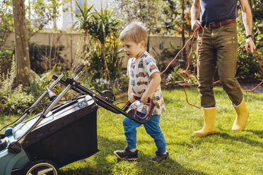 Toddler boy mowing the lawn with his father - MFF05560