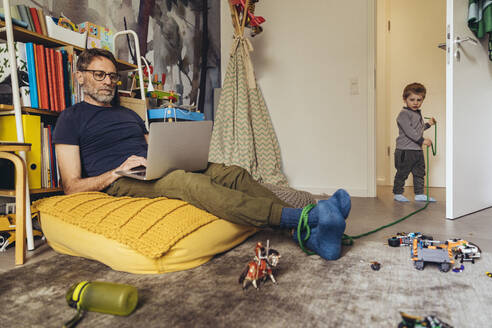Son tying his father working on laptop in children's room - MFF05575