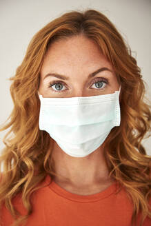 Portrait of red-haired woman wearing a protective mask at home - JHAF00075