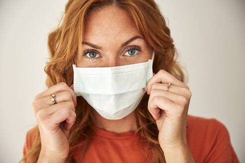 Portrait of red-haired woman wearing a protective mask at home - JHAF00078