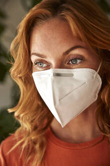 Portrait of red-haired woman wearing a protective mask at home - JHAF00081