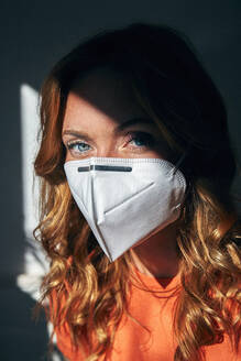 Portrait of red-haired woman wearing a FFP2 mask at home - JHAF00087