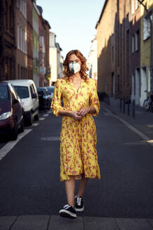 Red-haired woman wearing a FFP2 face mask and walking on empty road - JHAF00090