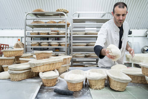 Baker putting dough into basket in bakery - FBAF01493