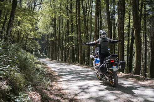 Motorcyclist on a trip on a forest road with arms outstretched - FBAF01508