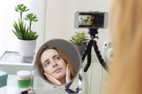 Young woman filming her beauty routine at home - AFVF05980
