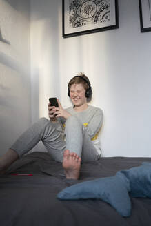 Portrait of laughing boy sitting on bed with headphones looking at cell phone - VPIF02330