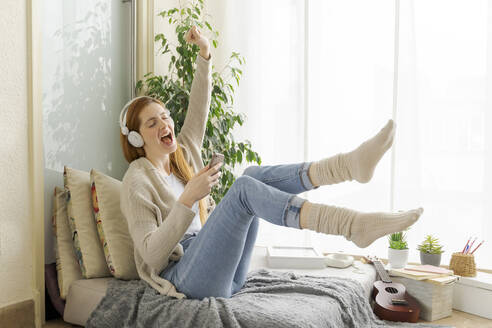 Carefree young woman listening to music with headphones at home - AFVF05990