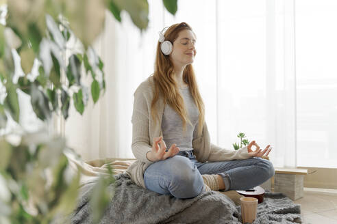 Young woman wearing headphones and practicing yoga at home - AFVF06011