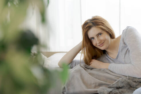 Portrait of smiling young woman relaxing at home - AFVF06023