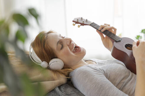 Carefree young woman with headphones and ukulele at home - AFVF06026