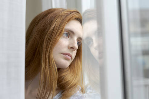 Portrait of serious young woman looking out of window - AFVF06032