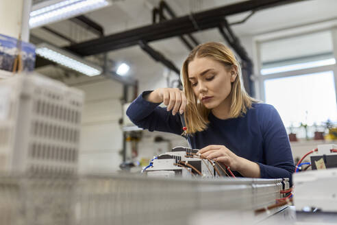 Female electrician working on circuitry in workshop - ZEDF03215