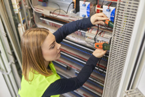 Female electrician working with voltmeter at fuse box - ZEDF03233