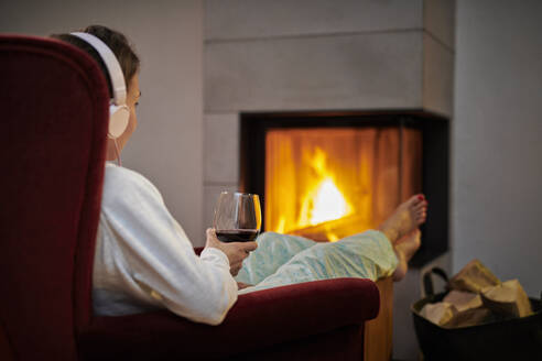 Woman sitting on armchair with glass of red wine listening music with headphones in front of fireplace - DIKF00453