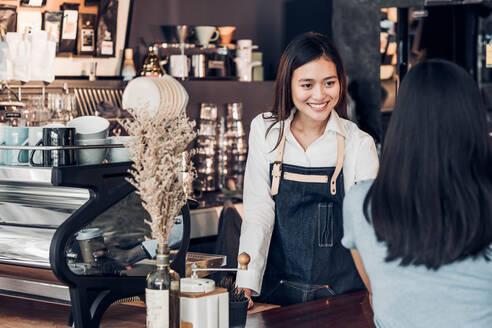 Smiling Owner Talking To Customer While Standing At Counter In Cafe - EYF04827