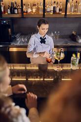 Barwoman preparing drinks in a bar - ZEDF03259