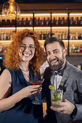 Portrait of happy couple socializing in a bar - ZEDF03262