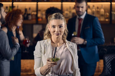 Portrait of a young woman having a cocktail in a bar - ZEDF03292