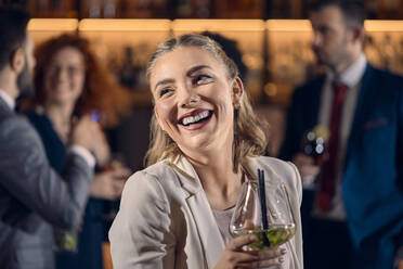 Portrait of a happy young woman having a cocktail in a bar - ZEDF03295