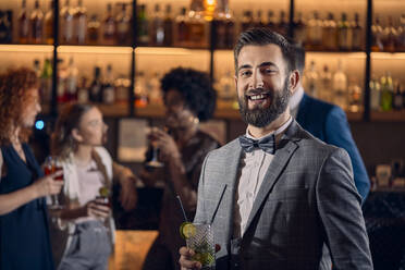 Portrait of a happy young man having a cocktail in a bar - ZEDF03298