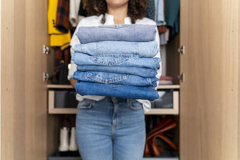 Woman standing on front of wardrobe holding stack of blue jeans - FMOF00969