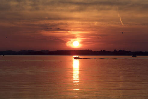 Germany, Bavria, Lake Chiemsee, Silhouette of lone motorboat sailing at moody sunset - ZCF00941
