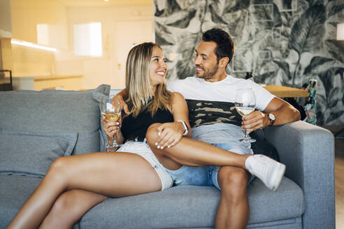 Happy couple sitting on the couch with glasses of white wine - MPPF00799