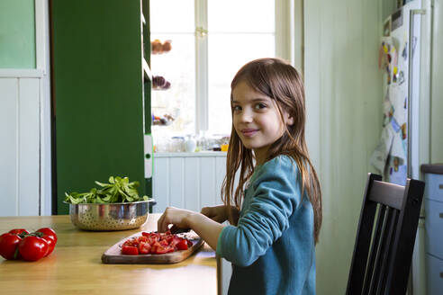 Smiling girl cutting tomatoes on chopping board in kitchen - LVF08809
