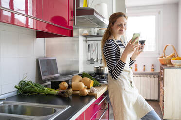 Woman drinking glass of red wine in the kitchen, while using smartphone - AFVF06042