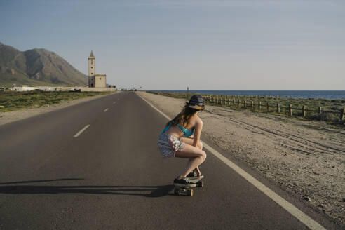 Back view of young woman skateboarding on asphalt road, Almeria, Spain - MPPF00813