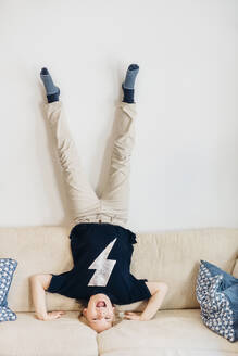 Carefree boy doing a headstand on couch in living room at home - MJF02446