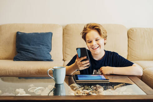 Happy boy using smartphone and tablet in living room at home - MJF02455