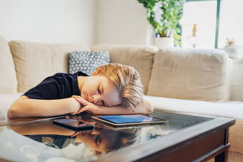 Boy lying on coffee table with smartphone and tablet taking a nap - MJF02458