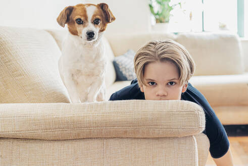Portrait of boy with dog lying on couch in living room at home - MJF02467