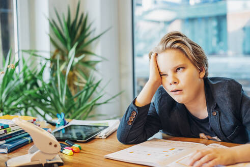 Frustrated boy sitting at desk with workbook - MJF02488