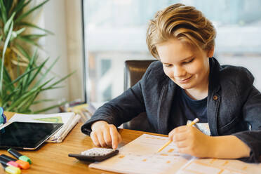 Smiling boy sitting at desk with workbook and pocket calculator - MJF02491