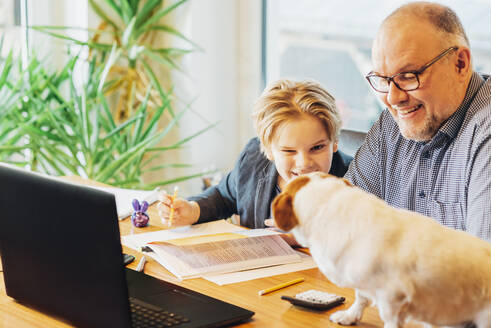 Father helping son doing homework with dog on desk - MJF02503