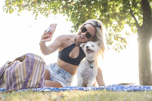 Beautiful woman taking a selfie with her dog on the beach, Costa Rica - AMUF00050