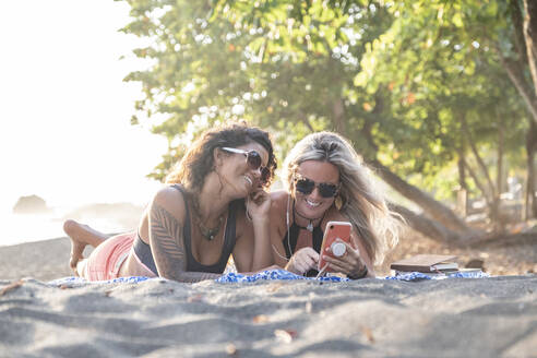 Two happy women listening music on the beach, Costa Rica - AMUF00053