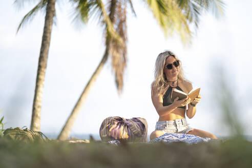 Beautiful woman reading a book at the beach, Costa Rica - AMUF00068