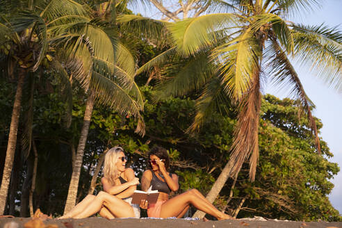 Two women reading a book on the beach, Costa Rica - AMUF00077