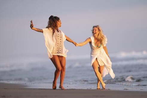 Two happy women taking selfie on the beach, Costa Rica - AMUF00083