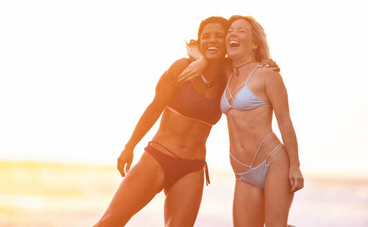 Two carefree women hugging on the beach at sunset, Costa Rica - AMUF00086