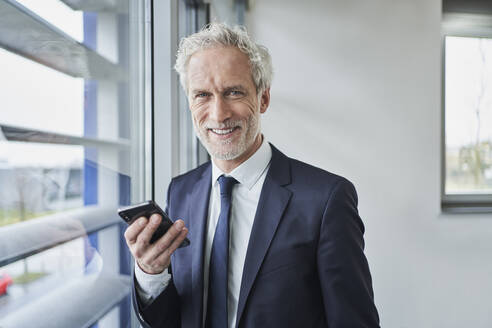 Portrait of smiling businessman holding cell phone at the window - RORF02133