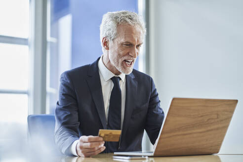 Successful businessman holding credit card and using laptop at desk in office - RORF02148