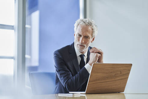 Focused businessman using laptop at desk in office - RORF02151