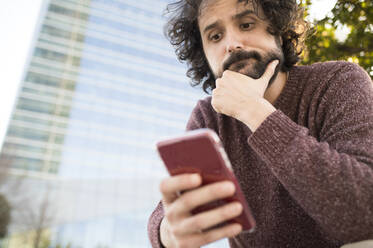 Portrait of bearded man looking at smartphone outdoors - KIJF02976