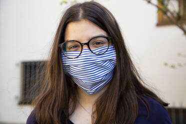 Teenage girl on her way to school, wearing face mask - LVF08819